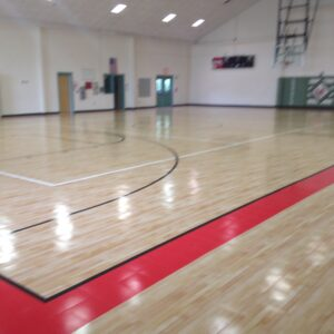 Indoor basketball court with shiny sports flooring.