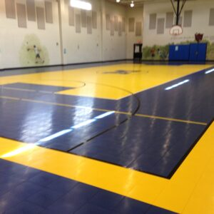 School gymnasium court with blue and yellow gym flooring and school logo.