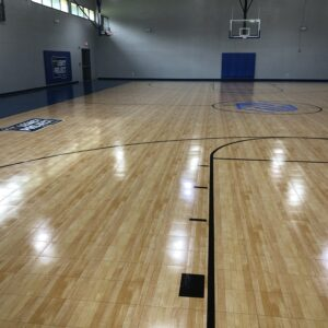 Indoor basketball court flooring with a Legacy Project logo.