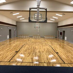 School auditorium with gymnasium flooring and basketball court.